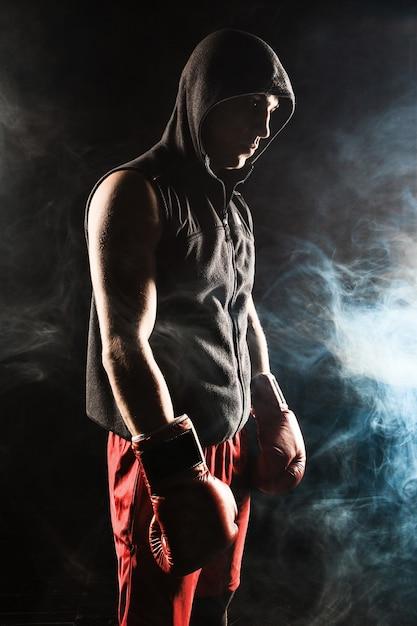 De jonge mannelijke atleet kickboksen staande op een achtergrond van blauwe rook Gratis Foto