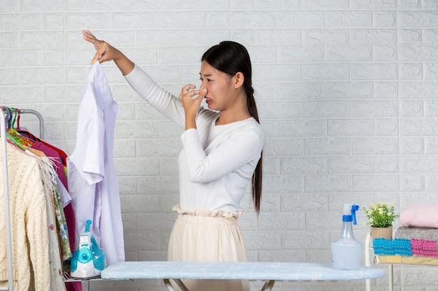 De jonge meid die stinkt, de geur van het afgewerkte shirt op de witte baksteen. Gratis Foto