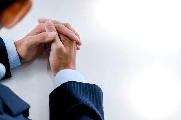 De jonge mens die op gesprek wachten en handen houden vouwde op een lijst. Premium Foto