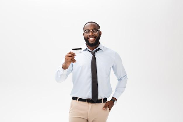 De jonge mens die zich in overhemd bevindt toont creditcard, bekijkt camera het glimlachen. Premium Foto