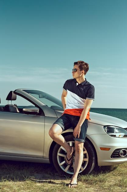 De jonge mens drijft een auto op het strand Premium Foto