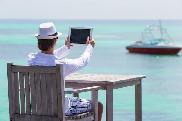 De jonge mens maakt een foto op tabletcomputer bij tropisch strand Premium Foto