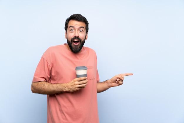 De jonge mens met baard die haalt koffie op verrast blauw weg en richt vinger aan de kant Premium Foto