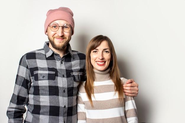 De jonge mens met een baard in een hoed en een plaidoverhemd koestert een meisje in een sweater op een geïsoleerd licht Premium Foto