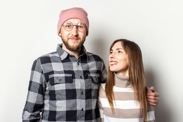 De jonge mens met een baard in een hoed en een plaidoverhemd koestert een meisje in een sweater op een geïsoleerde lichte achtergrond. Premium Foto