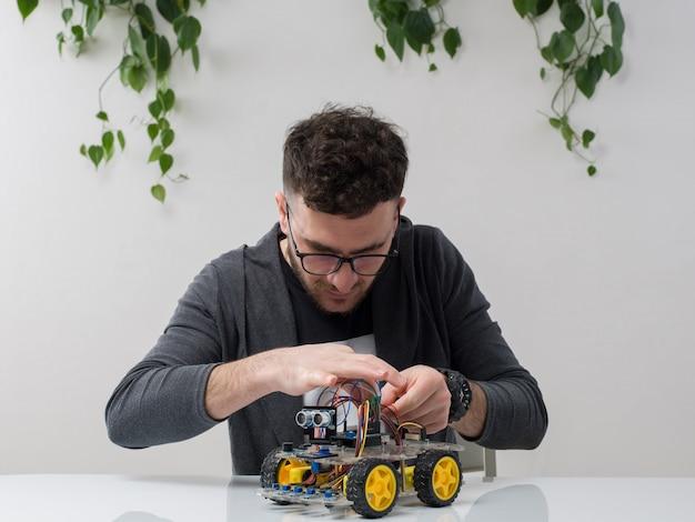 De jonge mensenzitting in bril let op grijze jas die machinestuk speelgoed samen met installatie op wit construeren Gratis Foto