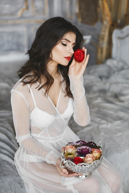 De jonge modelvrouw met perfect lichaam in witte lingerie en in peignoir zit op een bed met vaashoogtepunt van bloemen Premium Foto
