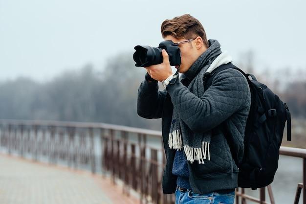 De jonge modieuze fotograaf houdt professionele camera, die foto's neemt. Gratis Foto