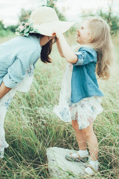 De jonge moeder en dochter op groen gras Gratis Foto