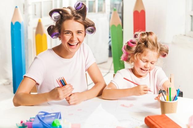 De jonge moeder en haar dochtertje tekenen thuis met potloden Gratis Foto