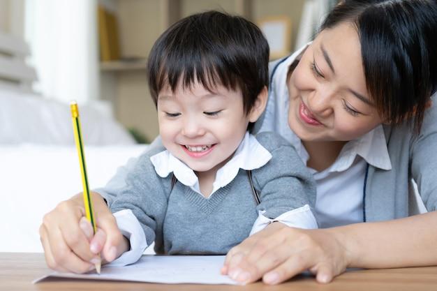De jonge moeder ving de hand van de zoon houdend een potlood aan mazelen opschrijven op witboek, kleuterschool thuis Gratis Foto