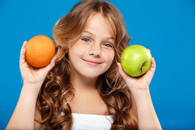 De jonge mooie appel en de sinaasappel van de meisjesholding over blauwe muur Gratis Foto