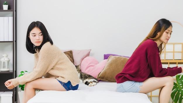 De jonge mooie aziatische minnaar van het vrouwen lesbische paar die na conflict elkaar in bedruimte thuis met humeurige emotie hebben beklemtoond. concept van lgbt-seksualiteit met overstuur en ongelukkige levensstijl samen. Premium Foto