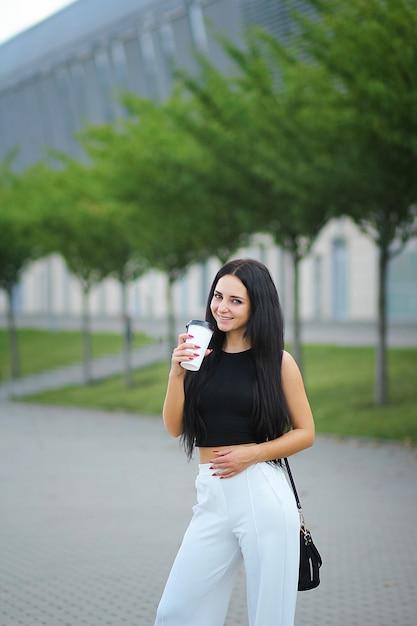 De jonge mooie bedrijfsvrouw drinkt dichtbij koffie naast de bureaubouw Premium Foto