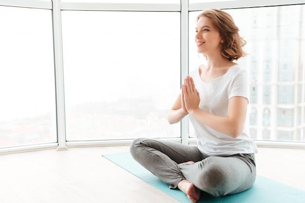 De jonge mooie damezitting dichtbij venster maakt yogaoefeningen. Gratis Foto