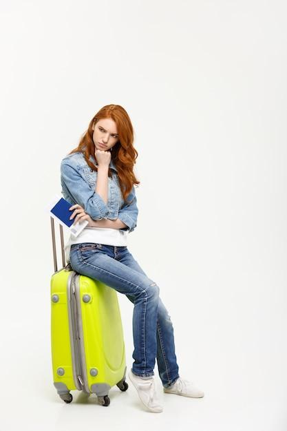 De jonge mooie kaukasische vrouw zit op suitecase en wacht op haar vlucht. Premium Foto