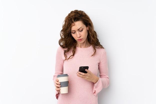 De jonge mooie koffie van de vrouwenholding om weg te nemen en mobiel Premium Foto
