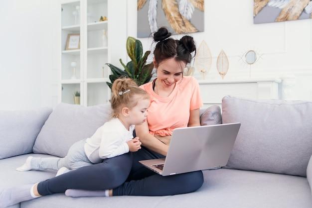 De jonge mooie moeder en haar kleine gelukkige dochter gebruiken laptop en glimlachen terwijl het zitten op bank thuis Premium Foto