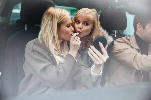 De jonge mooie vrouw die make-up doet bekijkt spiegel Gratis Foto