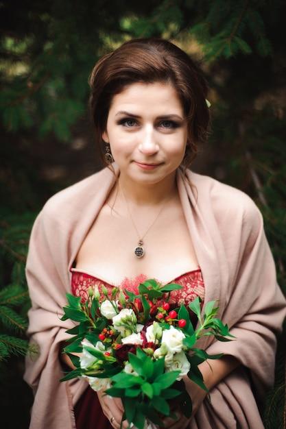 De jonge mooie vrouw in een trouwjurk met een boeket Premium Foto