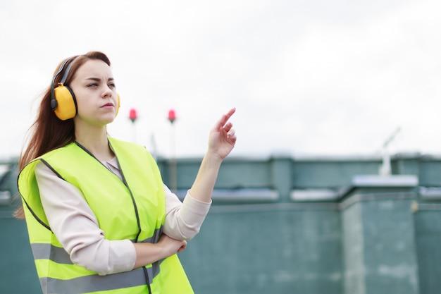 De jonge mooie vrouw in het groene westen en de oorbeschermers bevinden zich op dak, greeptablet Premium Foto