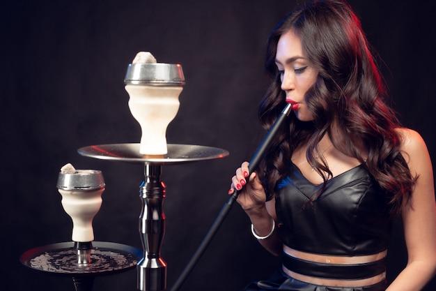 De jonge mooie vrouw in het zwarte kleding roken en ademt waterpijp uit Premium Foto