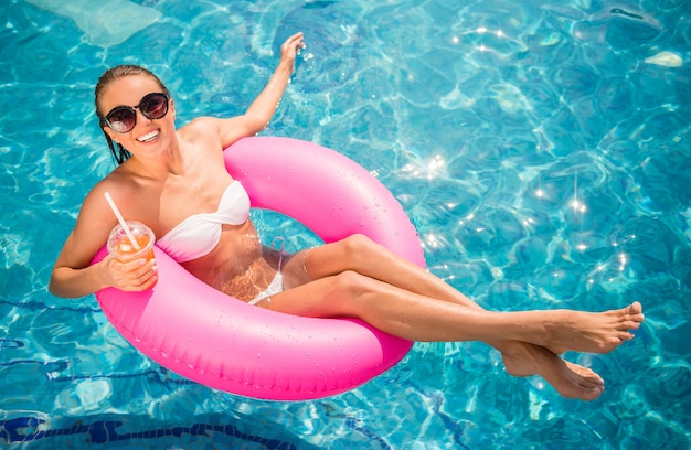 De jonge mooie vrouw ontspant in zwembad. Premium Foto