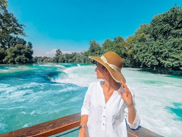 De jonge mooie vrouw staat dicht op de manavgat-waterval op Premium Foto