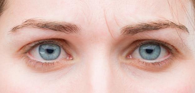 De jonge mooie vrouwen blauwe ogen sluiten omhoog. droevige uitdrukking Premium Foto