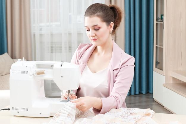 De jonge naaistervrouw naait kleren op naaimachine. Premium Foto