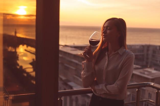 De jonge persoon ontspant en drinkt een glas rode wijn op het balkon bij zonsondergang in de avond Premium Foto