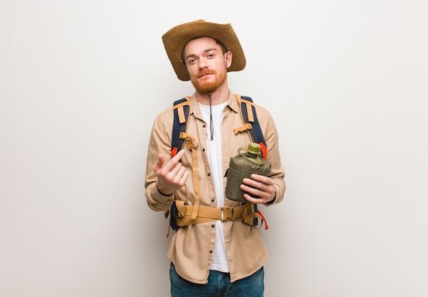 De jonge redhead ontdekkingsreizigermens die uitnodigen te komen. hij houdt een veldfles vast. Premium Foto
