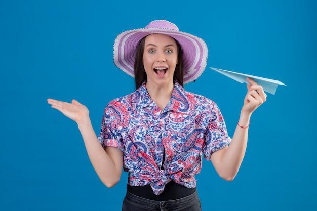 De jonge reizigersvrouw die in de holdingsdocument van de de zomerhoed vliegtuig verrast en gelukkig kijken met overhandigt overhandigt blauwe muur Gratis Foto