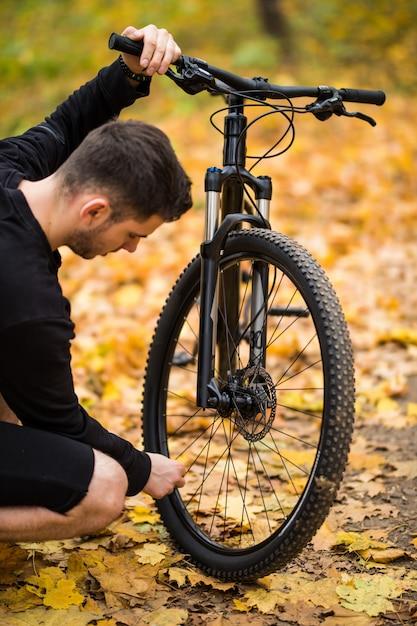 De jonge ruiter van de ruitermens heeft probleem met laag wiel in de herfstpark Gratis Foto