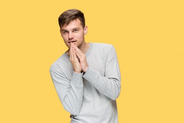De jonge serieuze man die voorzichtig kijkt en geheim spreekt Gratis Foto