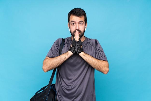 De jonge sportmens met baard houdt palm samen Premium Foto