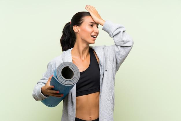 De jonge sportvrouw met mat over geïsoleerde groene muur heeft iets gerealiseerd en de oplossing voorgenomen Premium Foto