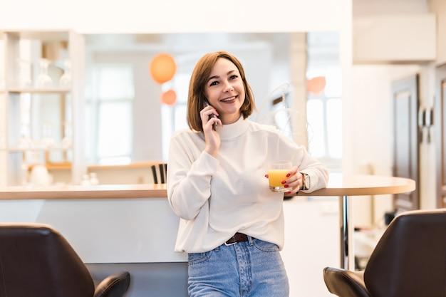 De jonge tedere dame spreekt op de telefoon en houdt een glas met jus d'orange Gratis Foto