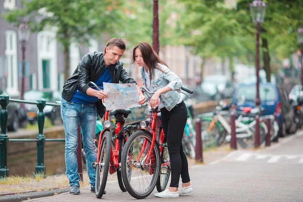 De jonge toeristen koppelen het bekijken kaart in europese stad. gezin van twee op vakantie in amsterdam Premium Foto