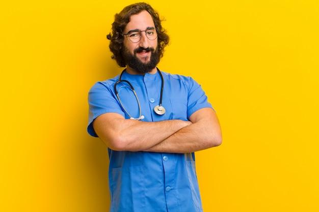 De jonge trotse verpleegstersmens stelt tegen gele achtergrond Premium Foto