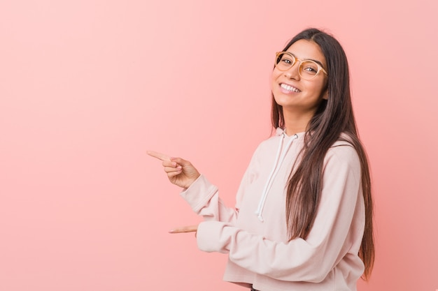 De jonge vrij arabische vrouw die een toevallige sport draagt kijkt opgewonden wijzend met weg wijsvingers. Premium Foto