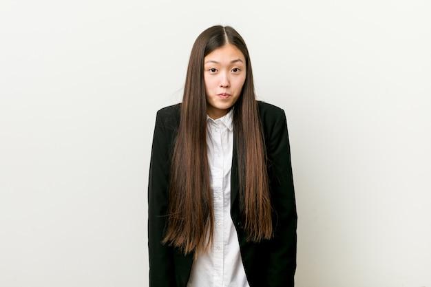 De jonge vrij chinese bedrijfsvrouw haalt schouders en open ogen op verward. Premium Foto