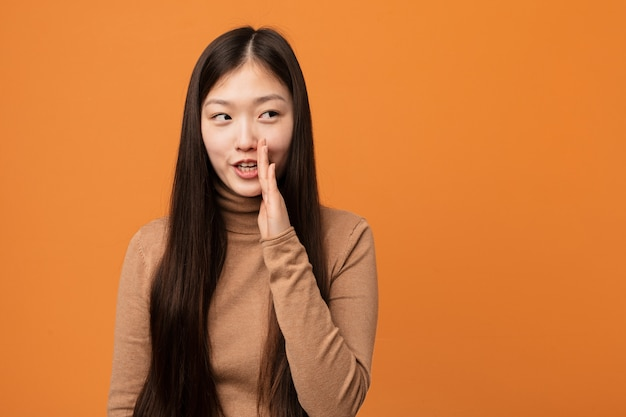 De jonge vrij chinese vrouw zegt een geheim heet remmend nieuws en kijkt opzij Premium Foto