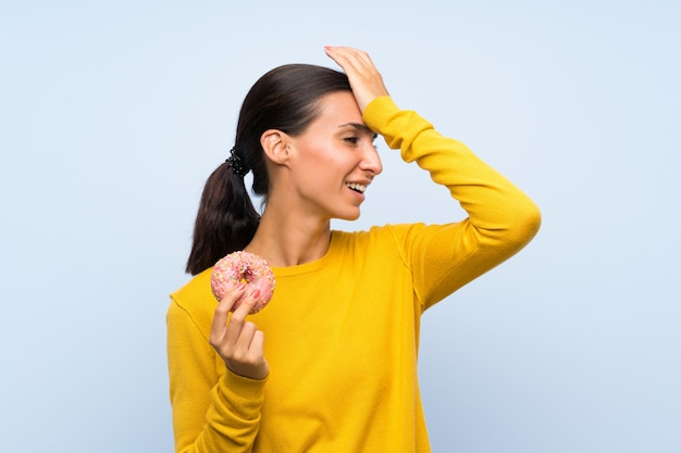 De jonge vrouw die een doughnut over geïsoleerde blauwe muur houdt heeft iets gerealiseerd en de oplossing voorgenomen Premium Foto
