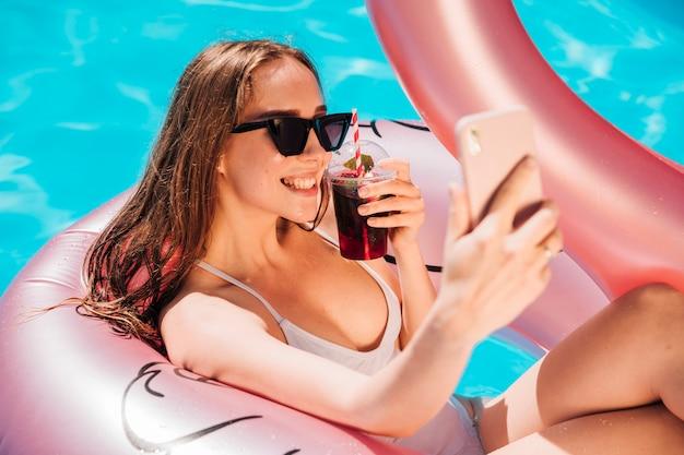 De jonge vrouw die een selfie neemt zwemt binnen ring Gratis Foto