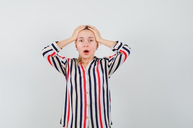 De jonge vrouw die haar hoofd bedekt met haar dient gestreepte blouse in en kijkt geschokt Gratis Foto