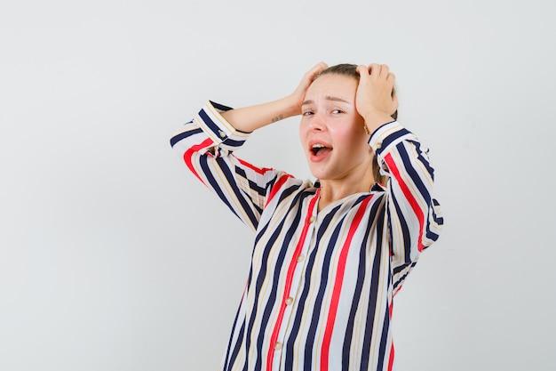 De jonge vrouw die haar hoofd behandelt met beide dient gestreepte blouse in en kijkt uitgeput Gratis Foto