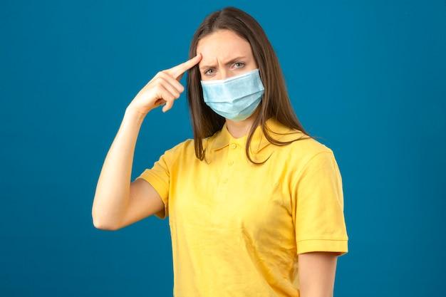 De jonge vrouw die in geel polooverhemd en medisch beschermend masker met vinger aan haar hoofd ontevreden richten kijkt op geïsoleerde blauwe achtergrond Gratis Foto