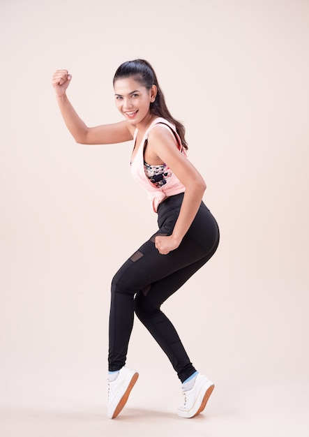 De jonge vrouw die oefeningspak draagt, die danstraining doet, voor oefening Premium Foto