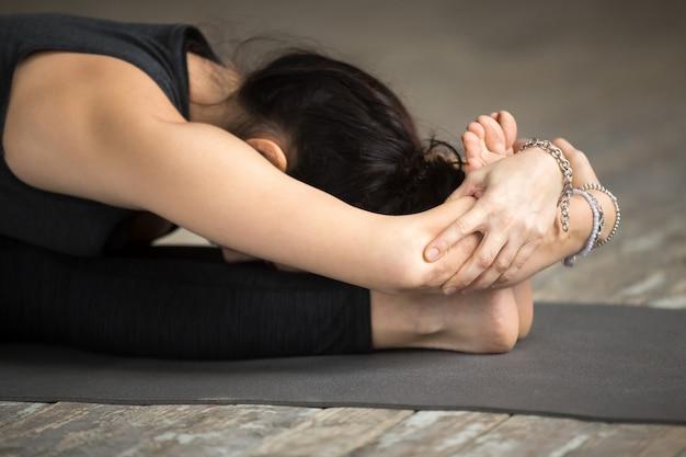 De jonge vrouw die paschimottanasana oefening doet, sluit omhoog Gratis Foto